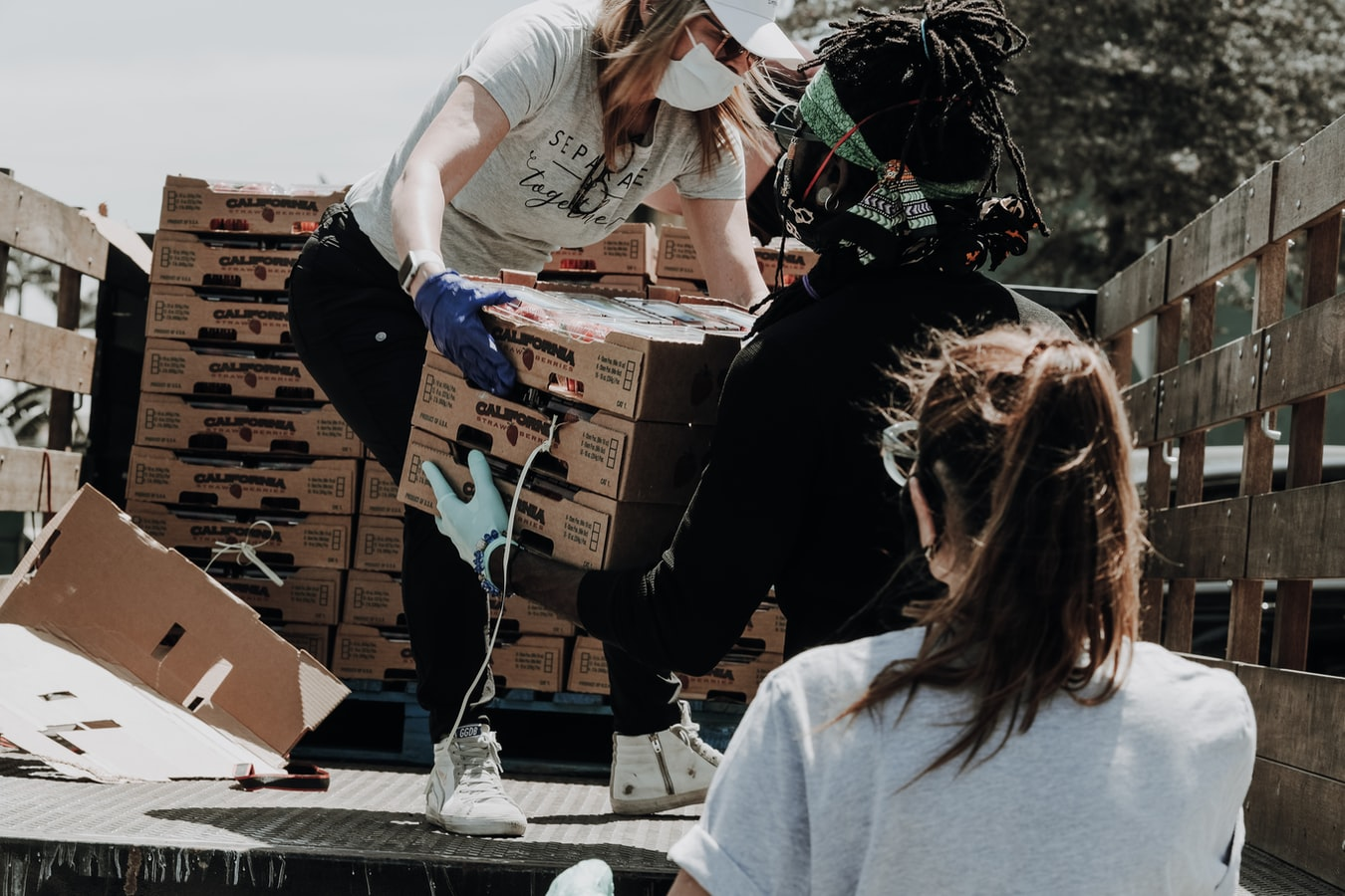 Volunteer workers unloading a flatbed truck of fresh produce