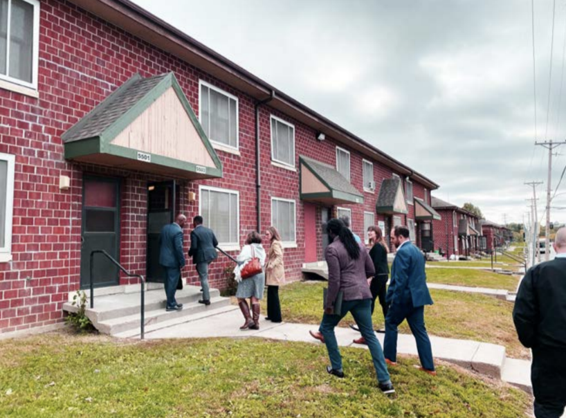 A group of stakeholders walking into a row house for an implementation meeting