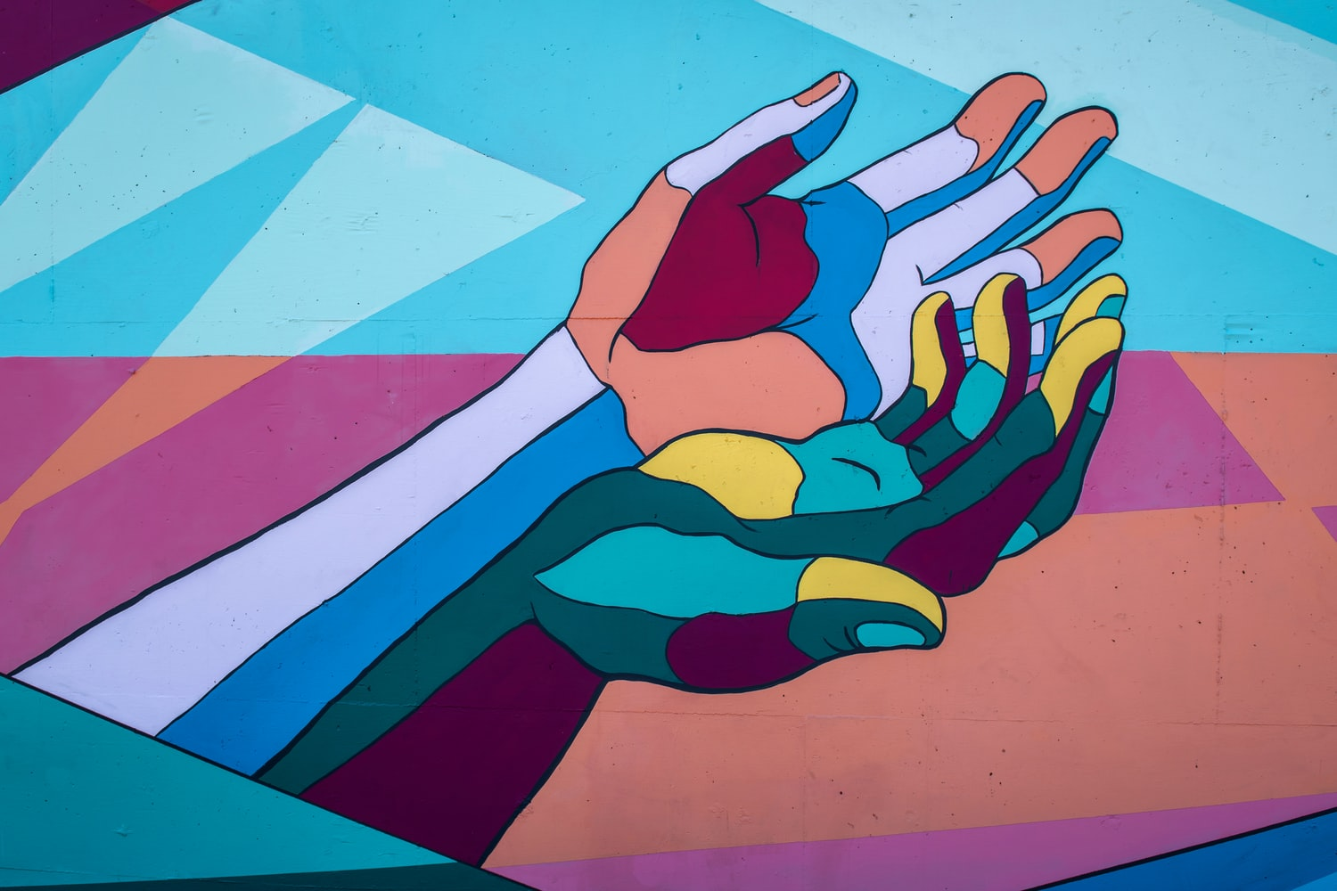 Close shot of a mural of painted hands outstretched